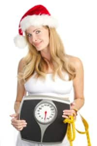 woman in santa hat with scale