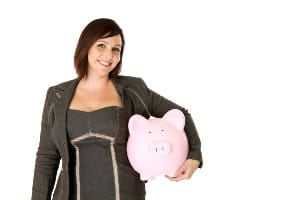 Middle-age woman in suit holding piggy bank.