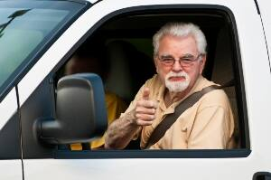 Senior male driving with thumbs up