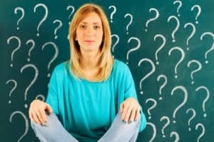 Confused woman in front of blackboard with question marks