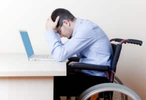 man in wheelchair looking despondent