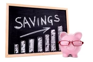 Savings written on chalkboard with piggybank